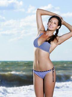 Милая модель сняв купальник позирует на пляже - фото