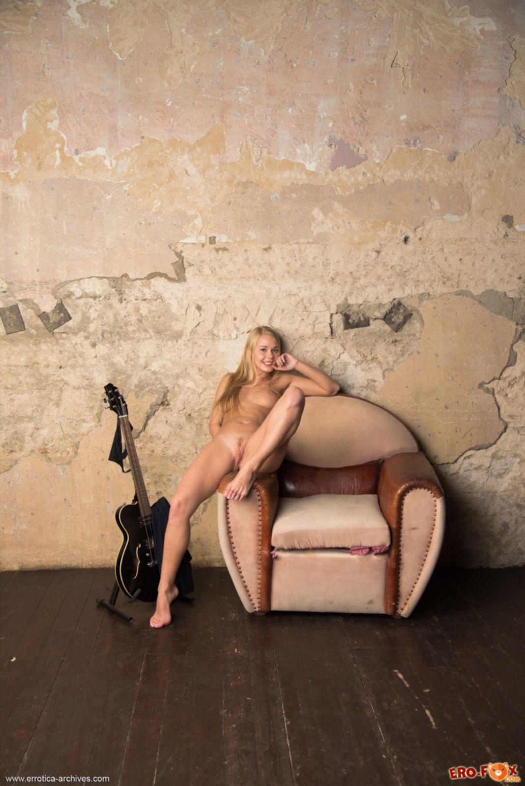 Блондинка с шикарными формами позирует голая в кресле - фото
