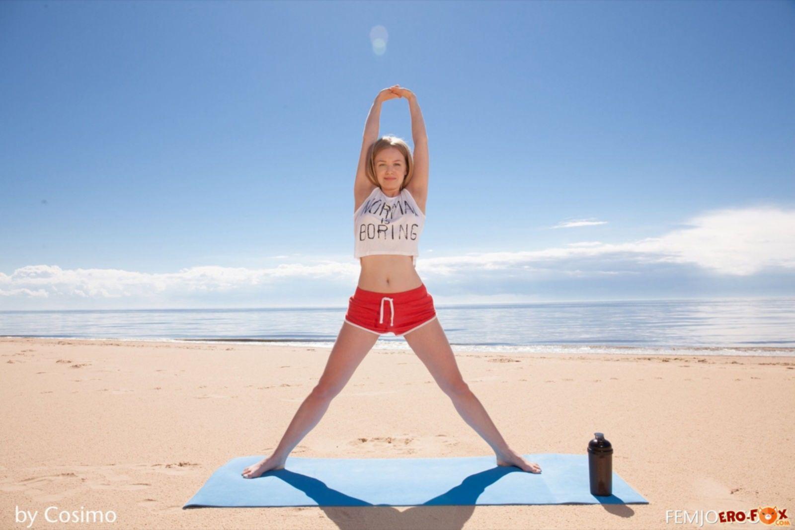 Голая девушка занимается йогой на пляже - фото