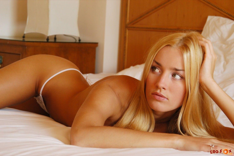 Блондинка в стрингах с упругими сиськами на кровати - фото