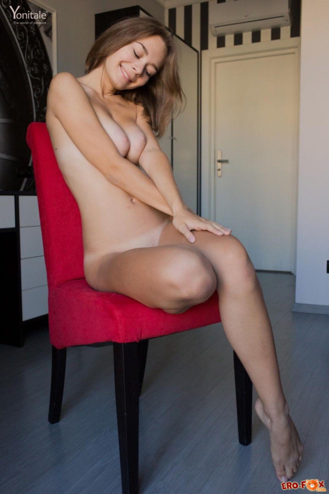 Стройная девка эротично позирует на красном стуле - фото