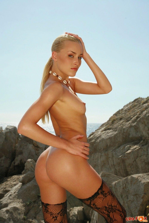 Стройная блондинка на море в чулках - фото