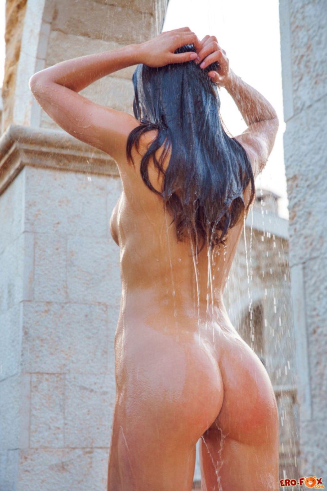 Худая голая брюнетка моется в душе - фото