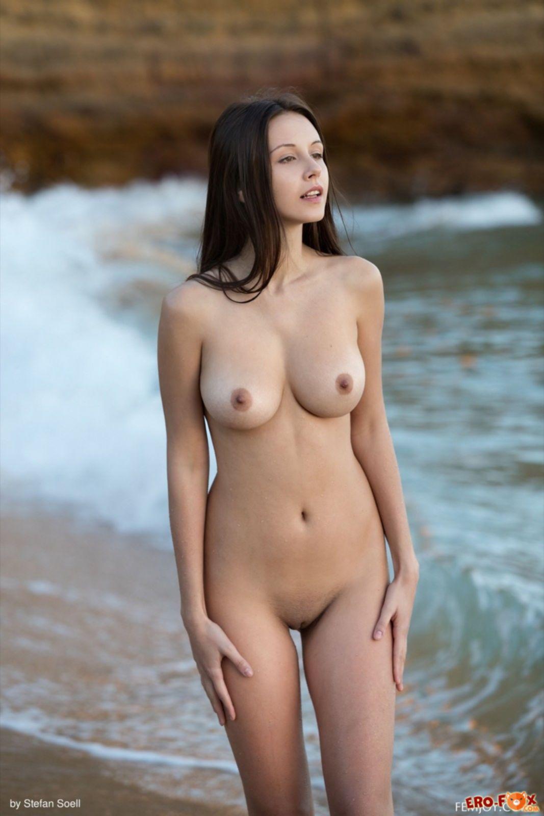 Высокая девушка с большой грудью купается в море - фото