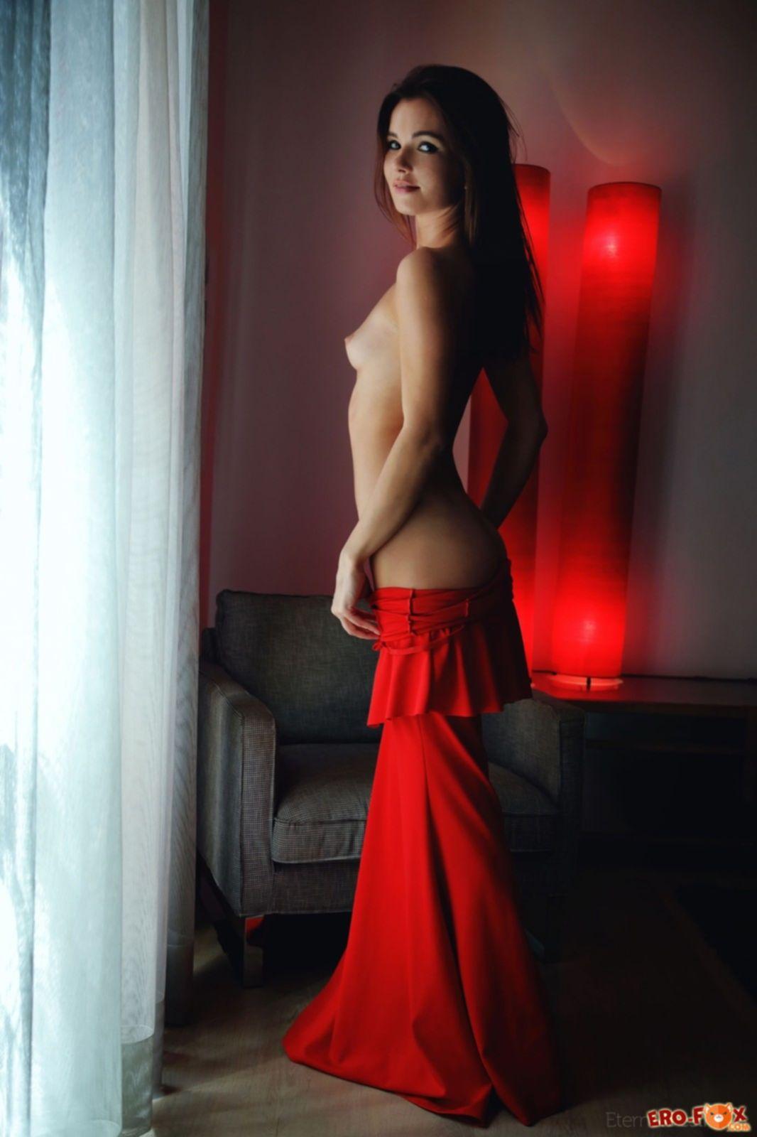 Брюнетка скидывает длинное платье и позирует в кресле - фото