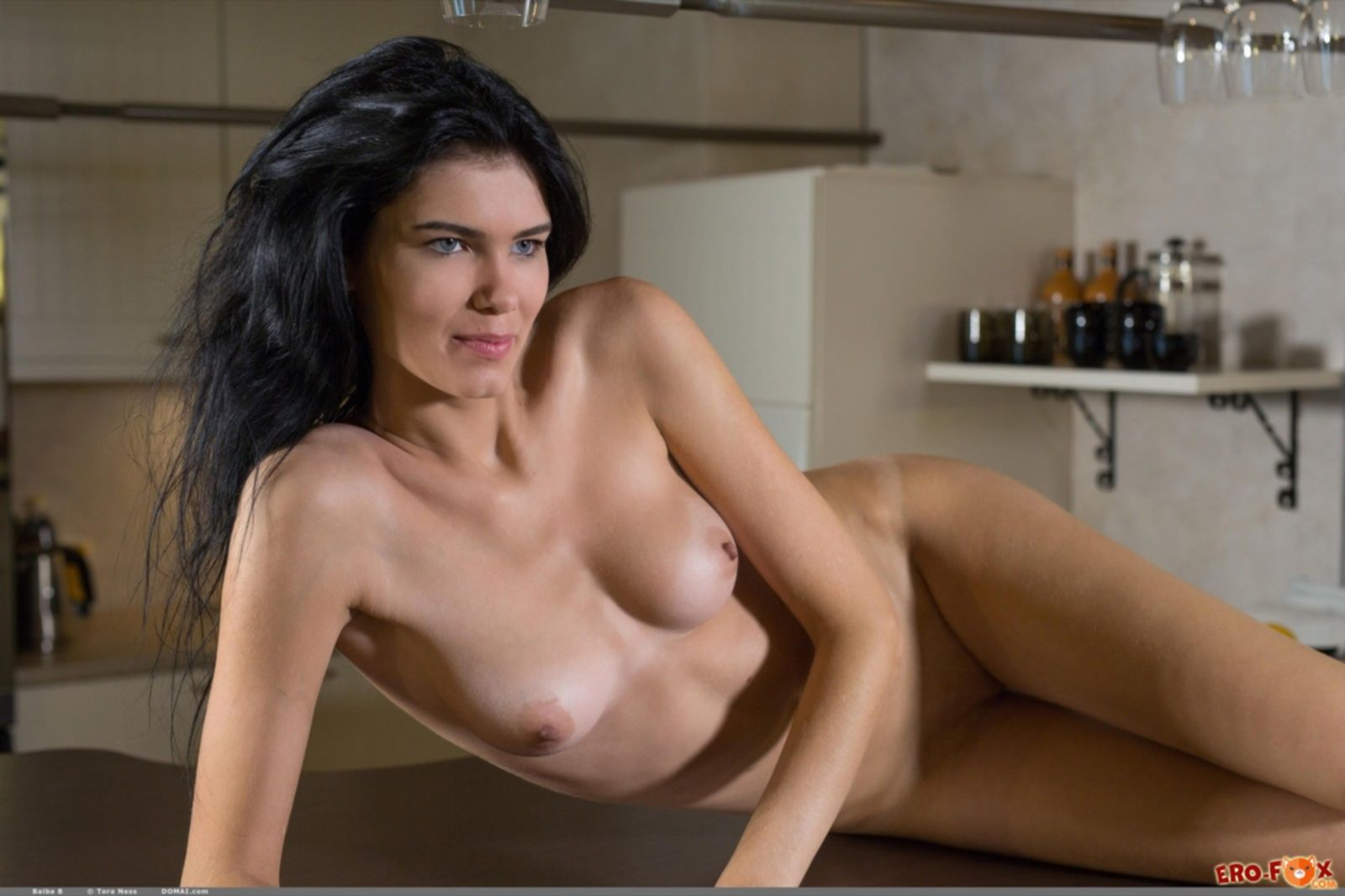 Высокая брюнетка голая позирует на кухне - фото