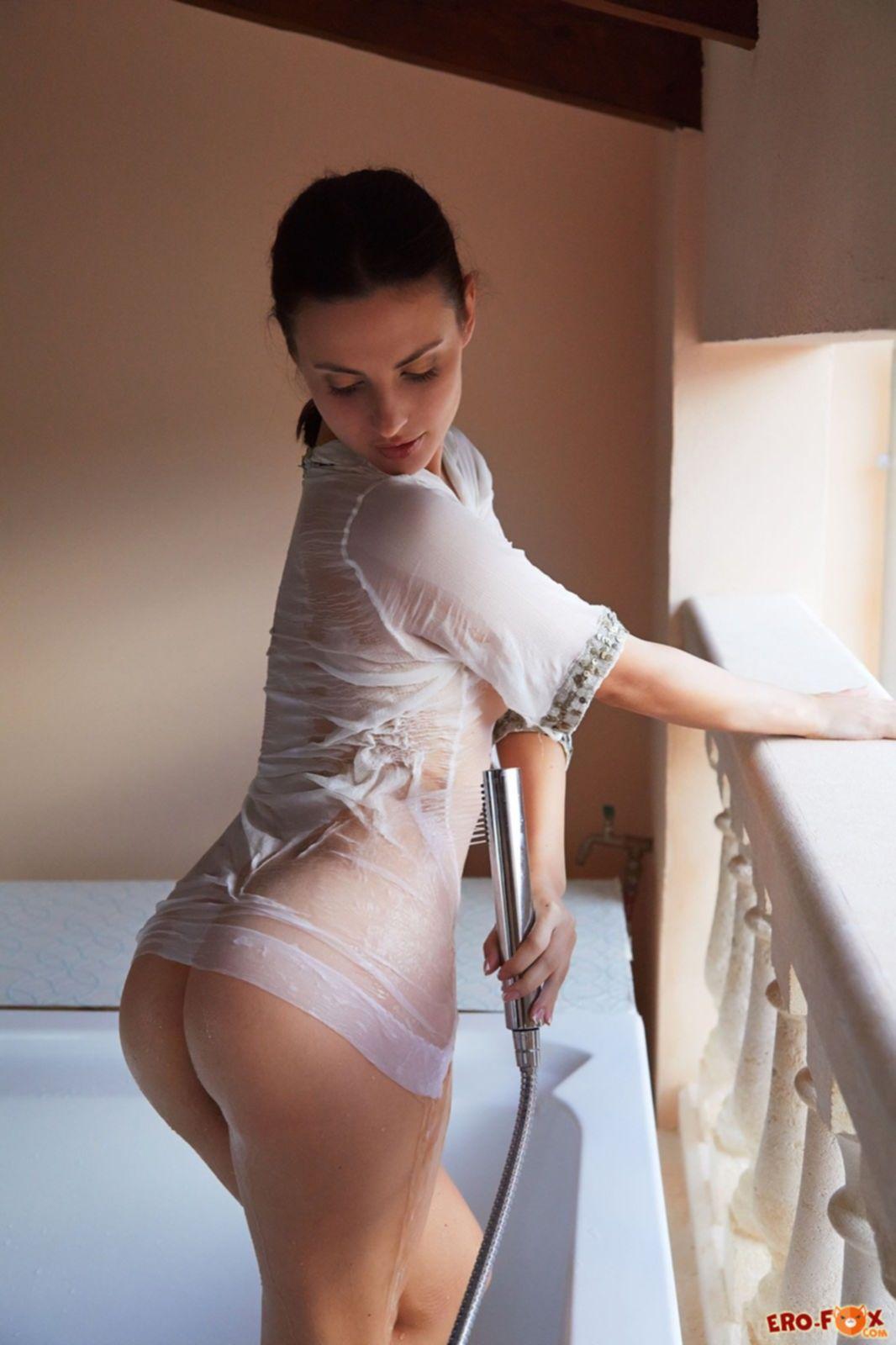 Сексапильная брюнетка в мокрой одежде в ванной - фото