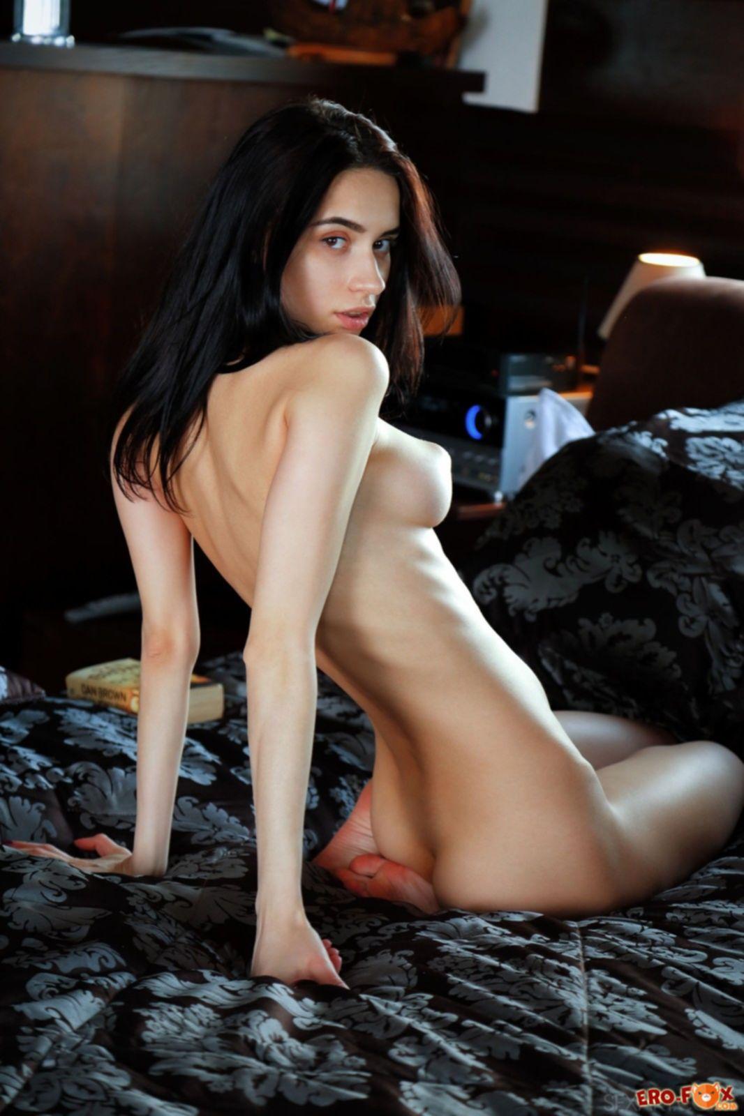 Худая брюнетка трогает бритую письку на кровати - фото