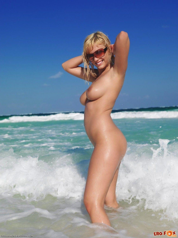 Грудастая голая девка стоит раком на пляже - фото