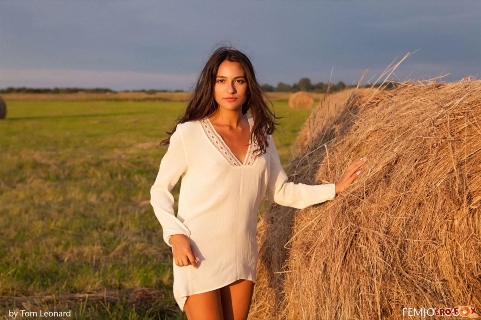 Молодая девушка голая в поле на стоге сена - фото