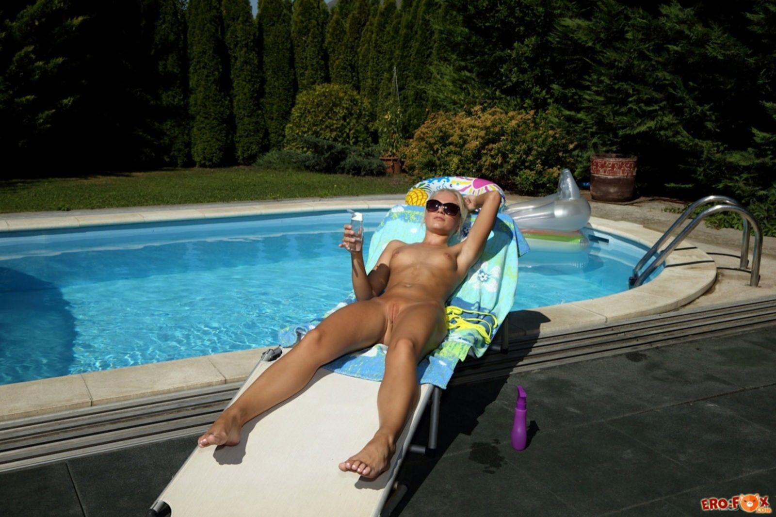 Белокурая худая крошка намазалась маслом у бассейна - фото