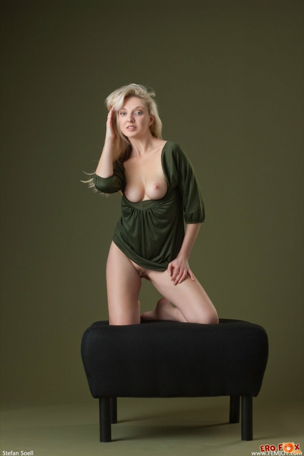 Белокурая модель с красивым телом красуется на пуфике - фото