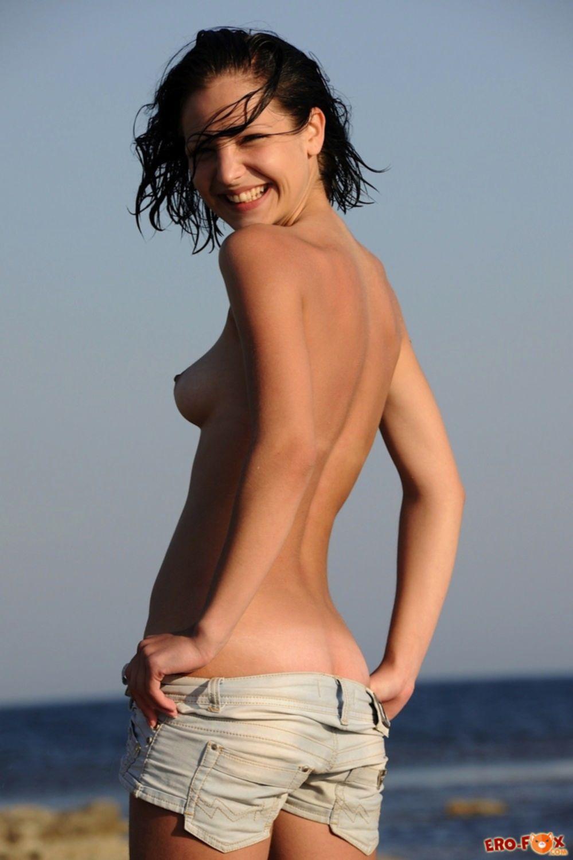 Маленькие сиськи брюнетки на пляже - фото