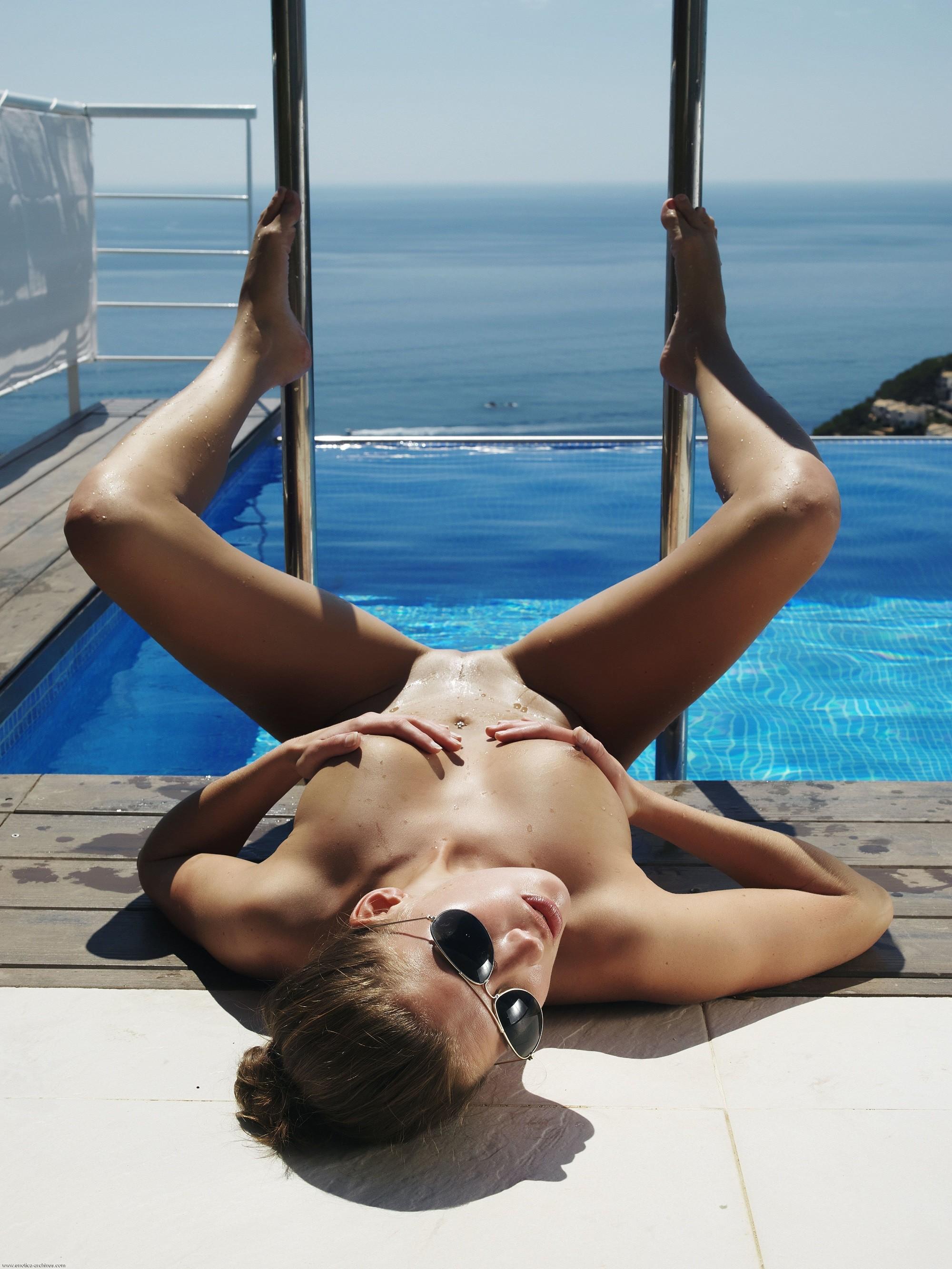 Голая девушка в очках нежится рядом с бассейном - фото