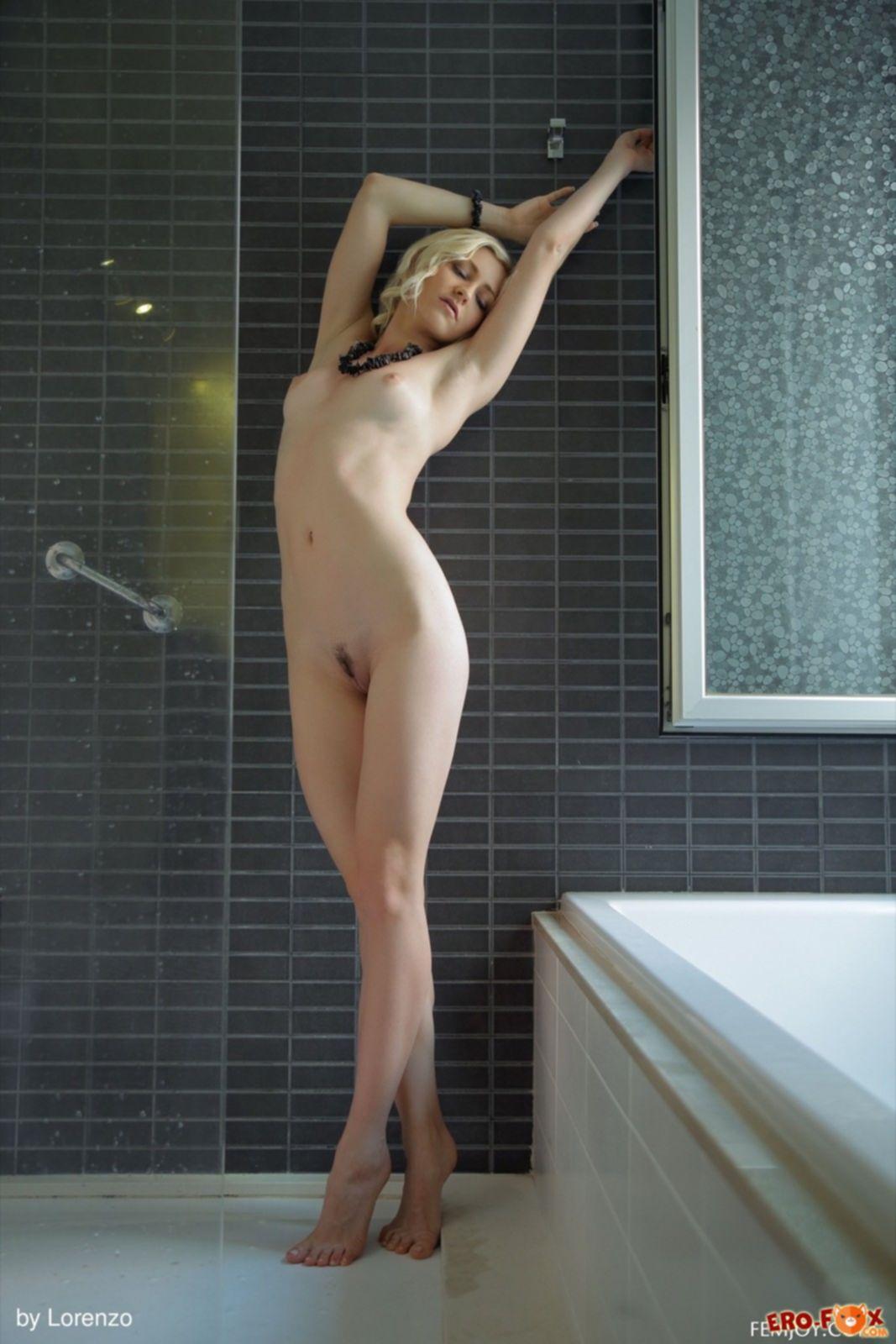 Голая блондинка мокрая лежит в ванне - фото