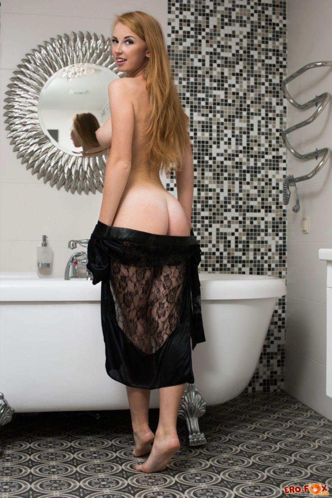 Блондинка в халате на голое тело позирует в ванной - фото